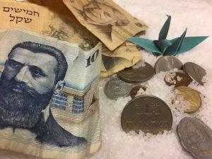 ברבור אוריגמי ירוק שמסמל רכות לצד יצירתיות ודיוק, מונח בין שטרות ומטבעות ישראלים מתקופות עבר. להמחשת המסר שביופי שקיים במכירות ערכיות.