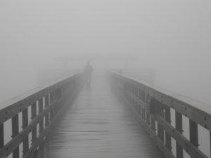 ערפל כבד. אדם פוסע על גשר לצידו השני, לא ניתן לראות מה יש מעברו השני של הגשר מכוון שערפל כבד מכסה הכל.
